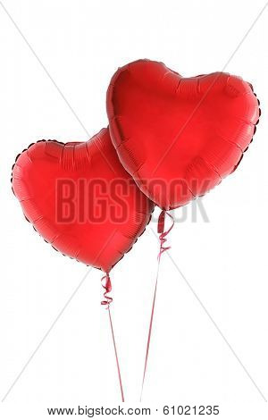 Two red heart balloons on white