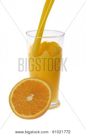 orange juice poured in tall glass with cut orange in foreground on white