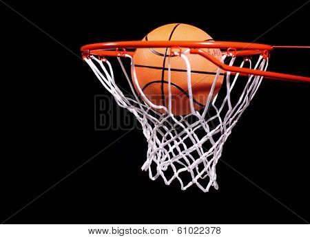 Basketball in hoop on black background