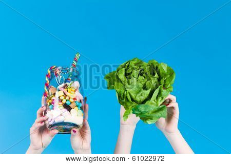 Young women with healthy and unhealthy food like salad and candy in studio, only the hands are showing