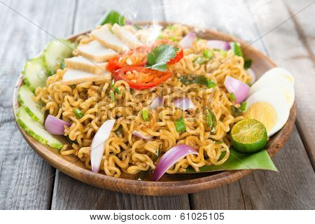 Malaysian style maggi goreng mamak  or spicy fried curry instant noodles.  Asian cuisine, ready to serve on wooden dining table setting. Fresh hot with steamed smoke.