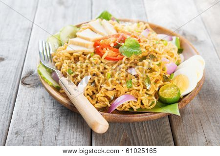Spicy fried curry instant noodles or Malaysian style maggi goreng mamak.  Asian cuisine, ready to serve on wooden dining table setting. Fresh hot with steamed smoke.