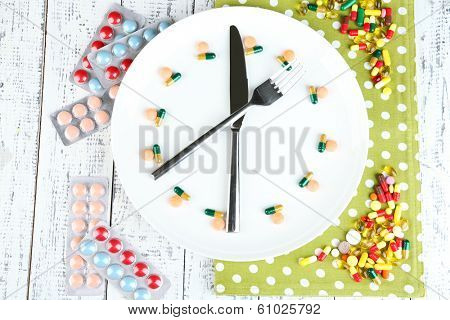 Medication schedule and meals. Conceptual photo. On color napkin, on wooden background