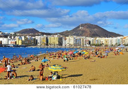LAS PALMAS, SPAIN - OCTOBER 13: Bathers in Las Canteras Beach on October 13, 2013 in Las Palmas de Gran Canaria, Spain. Due to the tropical weather, the locals can go to the beach almost all year