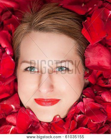 rose petals around a beautiful woman's face.