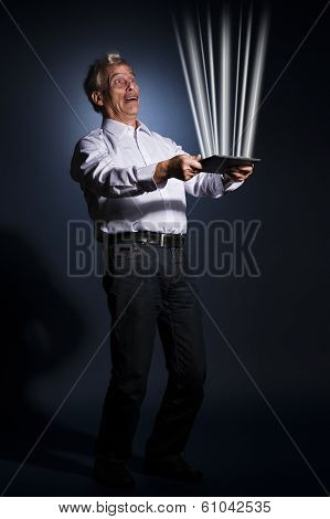 Businessman Holding A Tablet Radiating Light