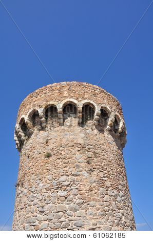 medieval stone tower against blue sky on a sunny day