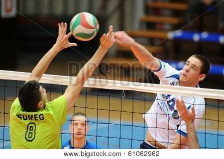 KAPOSVAR, HUNGARY - FEBRUARY 25: Tamas Vajda (white 14) in action at a Hungarian National Championship volleyball game Kaposvar (white) vs. Sumeg (green), February 25, 2014 in Kaposvar, Hungary.