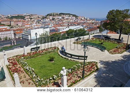 Lisbon, Portugal - May 26, 2013: Miradouro de Sao Pedro de Alcantara (Belvedere) in the Bairro Alto District and a view of the Baixa District and the Sao Jorge Castle of Lisbon, Portugal -