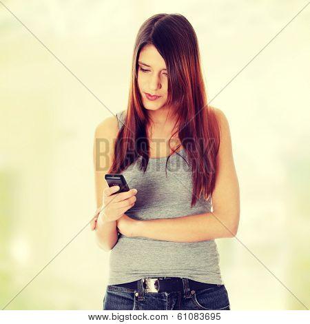 Teen girl using cell phone sending sms