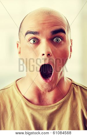 Closeup portrait of a shocked young man looking straight