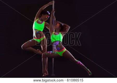 Two slender girls with UV makeup posing near pylon