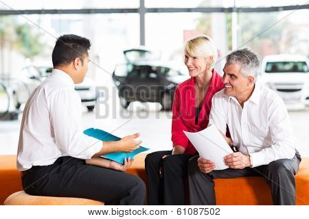 vehicle salesman explaining contract to senior couple before buying a car