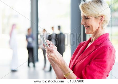 beautiful middle aged businesswoman reading email on smart phone