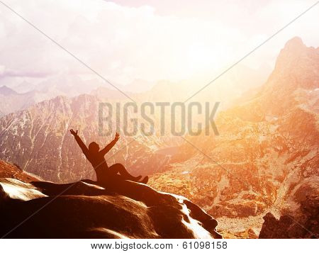 A happy man sitting on the peak of a mountain with hands raised admiring breathtaking view at sunset