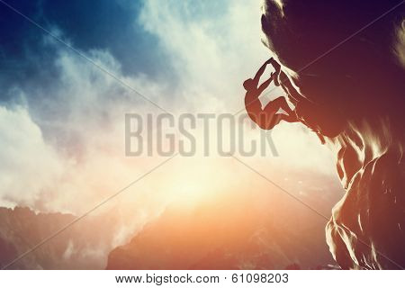 A silhouette of man climbing on rock, mountain at sunset. Adrenaline, strenght, ambition poster