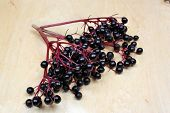stock photo of elderberry  - Healthy elderberry fruit on a wooden table - JPG
