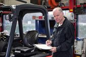 Experienced Mechanic working through a checklist before a brand new forklift is delivered and commis