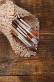 Brushes in sackcloth napkin on wooden background