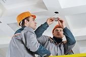 stock photo of lineman  - electrician worker in uniform installing or replacing spot light lamp into ceiling - JPG