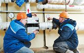 two repairman engineer of fire engineering system or heating system open the valve equipment in a bo