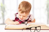 picture of librarian  - Happy funny baby girl in glasses reading a book in a library - JPG