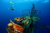 stock photo of wrecking  - Free diver exploring the ship wreck in tropical clear sea - JPG