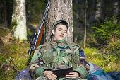 Sleeping recruit with tablet PC and optical rifle in forest