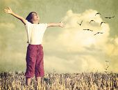 foto of grass bird  - Colorized kid breathing fresh air with birds flock flying in background - JPG