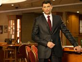 Handsome brunette wearing suit and necktie in luxury interior