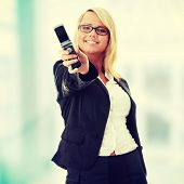 Attractive young business women with cellular phone - focus on phone
