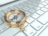 Online navigation. Compass on laptop keyboard. 3d