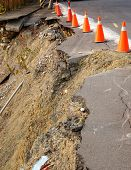 stock photo of landslide  - Red and white traffic cones on a road that has been damaged by a landslide - JPG