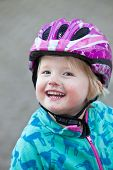 pic of vivacious  - Beautiful vivacious young girl with a joyful smile wearing a colourful purple safety helmet playing outdoors - JPG