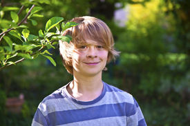 stock photo of cheeky  - cute smiling boy with cheeky smile in the garden - JPG