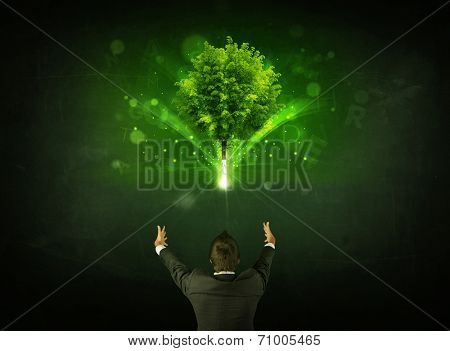 Young businessman standing with a glowing tree and letters above his head