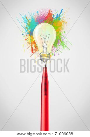Pen close-up with colored paint splashes and lightbulb concept