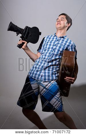 Portrait Of A Young Cameraman With Old Movie Camera And A Suitcase In His Hand