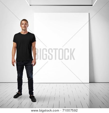 Man wearing blank t-shirt and white poster on a wall