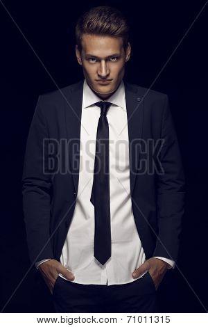 Cool Businessman Standing On Dark Background