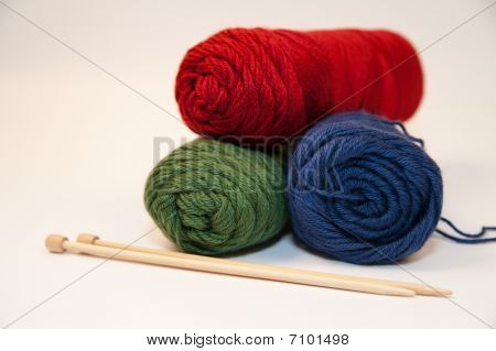 Three Skeins of Yarn and Knitting Needles