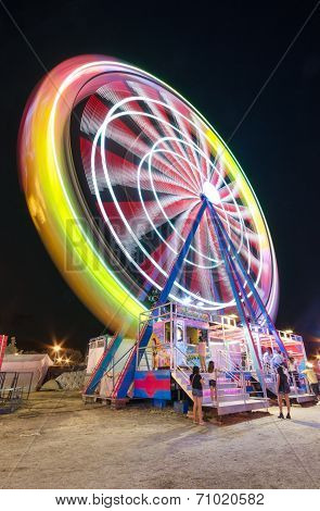 Long exposure picture of a Ferrys wheel rotating in a small local amusement park.