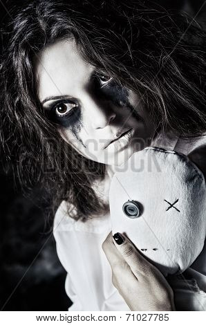 Horror Shot: The Sad Strange Girl With Moppet Doll In Hands. Closeup