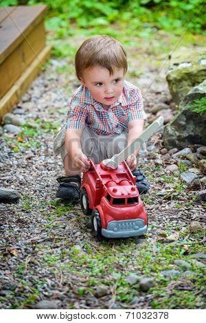 Toddler Playing With A Toy Fire Truck Outside - Series 1