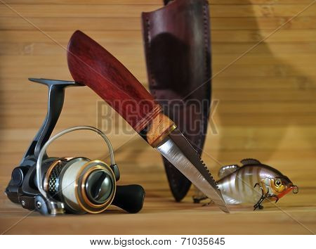 Knife For Cleaning Fish On A Background Of A Fishing Reel And Lure On A Wooden Background