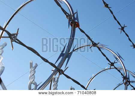 Metal fence with razor wire on top