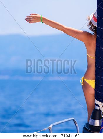 Happy woman on sailboat, back side of cheerful girl with raised up hand enjoying majestic seaview, summer vacation concept