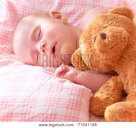 Portrait of adorable newborn baby sleeping on cute pink pillow with soft toy of teddy bear, day dreaming, love and childcare concept