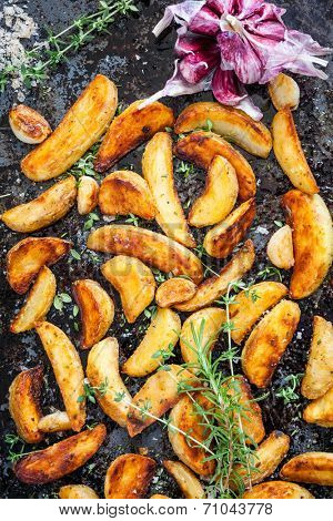 Roasted potato wedges with herbs and garlic on a baking tray