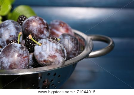 Ripe sweet plums in metal colander, on wooden table